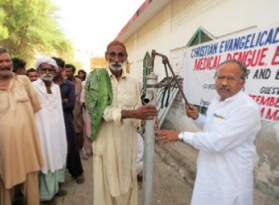 Saleem Massey (right) hands out water pumps in Nawab Shah, Pakistan during a flood relief event in 2012.